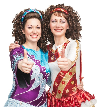 Happy Irish dancers showing thumbs up sign